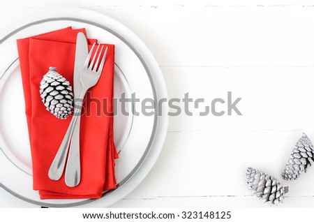 Christmas table setting in red and white, modern simple design with white pine cone as xmas element - stock photo