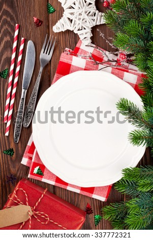 Christmas table setting with gift box and fir tree on wooden table. Top view - stock photo