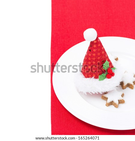 Christmas table setting with red cap and cookies, isolated on white - stock photo