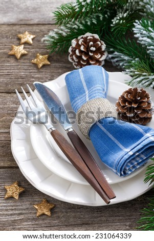 Christmas table setting with spruce branches and stars on wooden background, top view, vertical - stock photo