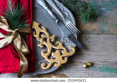 Christmas table setting with vintage silverware and pine tree branch in vase and christmas decorations on the rustic background - stock photo