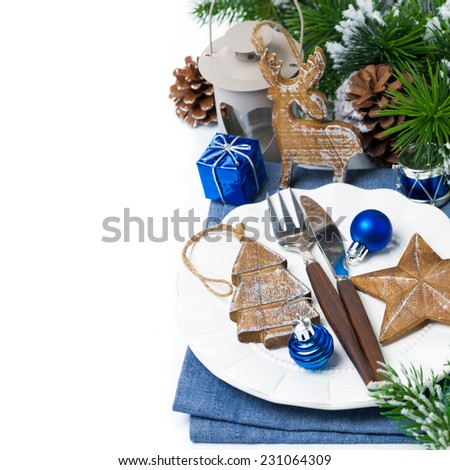 Christmas table setting with wooden decorations and spruce branches over white, close-up, vertical - stock photo