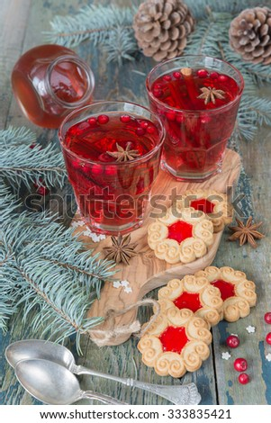 Christmas table - two glasses of red hot mulled wine with spices and cookies with bilberry jam surrounded by fir branches and cones