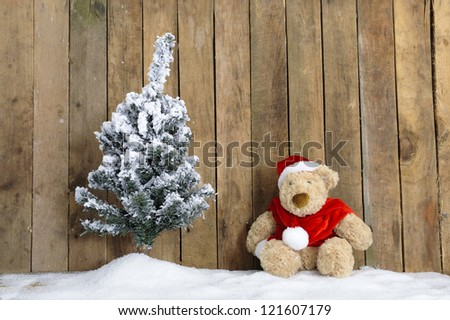 christmas teddy bear sitting in the snow, wooden background - stock photo