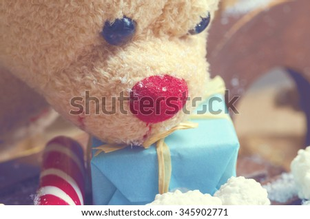Christmas teddy bear with candy cane and blue present. Selective focus - stock photo
