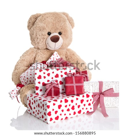 Christmas: Teddy bear with pile of red and white birthday or valentines presents on white background. - stock photo