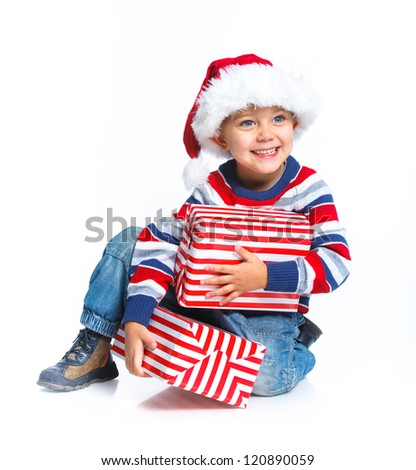 Christmas theme - Closeup smiling little boy in Santa's hat with gift box, isolated on white - stock photo
