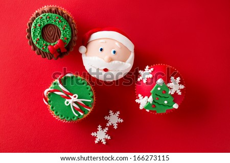 Christmas theme cupcakes in traditional red green colors and candy elements from overhead  - stock photo