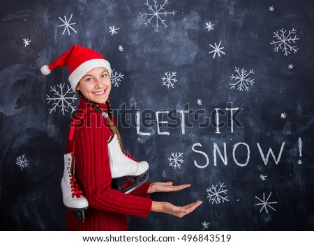 Christmas theme - lets it snow. Happy cute girl in studio in santa hat