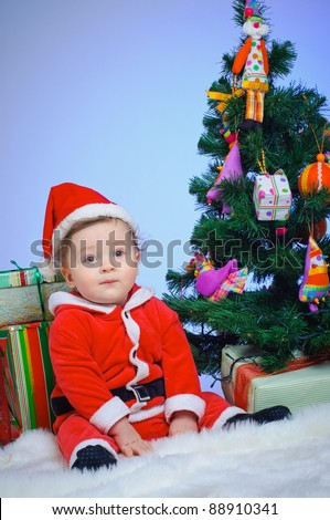Christmas theme: little Santa - Surprised baby boy with gifts. Vertical view