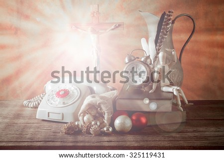 Christmas theme on waiting midnight telephone call for celebration with vintage analog telephone Christian cross old grunge alarm clock old book wood doll feather bronze jar and bag of gift fine tuned - stock photo