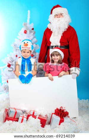 Christmas theme: Santa Claus and little children holding white board. - stock photo