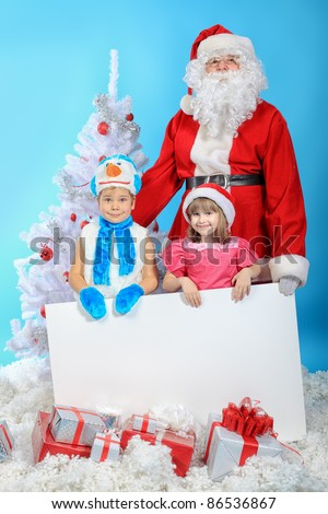 Christmas theme: Santa Claus and little children holding white board.