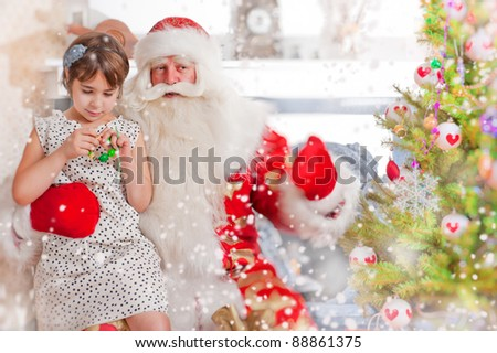 Christmas theme: Santa Claus and little girl having a fun. Indoors at home near christmas tree. - stock photo