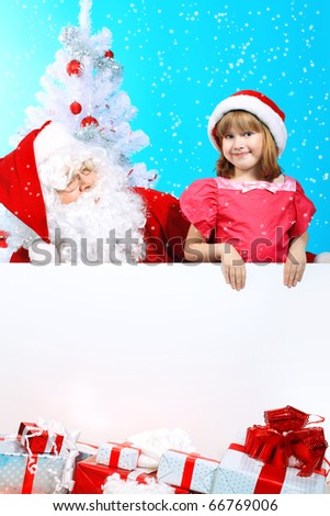 Christmas theme: Santa Claus and little girl holding white board.
