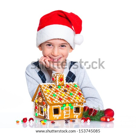 Christmas theme - Smiling boy in Santa's hat with gingerbread house, isolated on white - stock photo