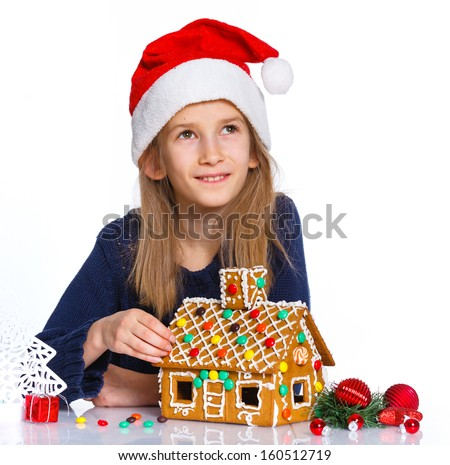 Christmas theme - Smiling girl in Santa's hat with gingerbread house, isolated on white - stock photo