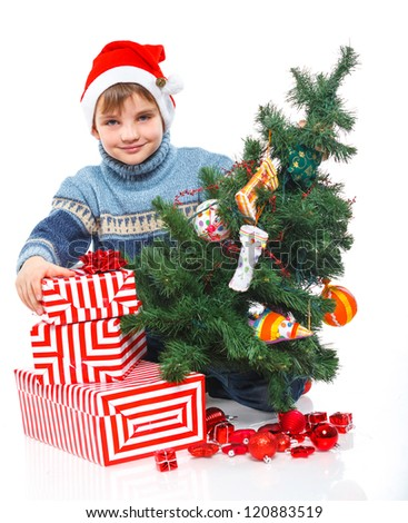 Christmas theme - Smiling little boy in Santa's hat with gift box and christmas tree, isolated on white - stock photo