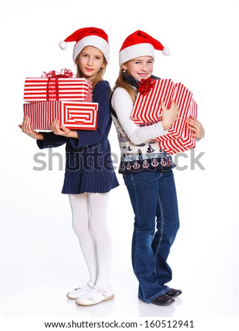 Christmas theme - Two smiling girl in Santa's hat with gift box, isolated on white