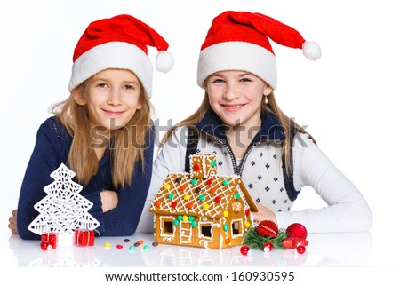 Christmas theme - Two smiling girl in Santa's hat with gingerbread house, isolated on white - stock photo
