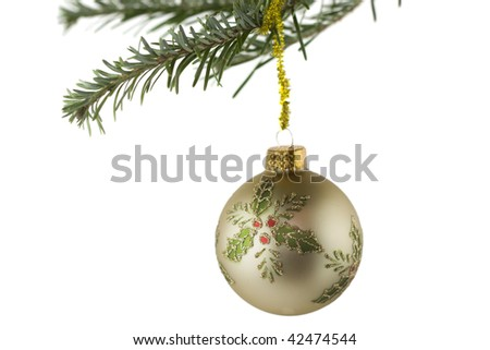 Christmas themed gold ornament with holly leaves hanging from fir branch