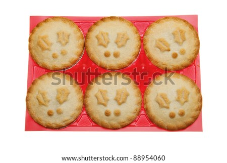 Christmas themed mince pies in a red plastic tray isolated against white