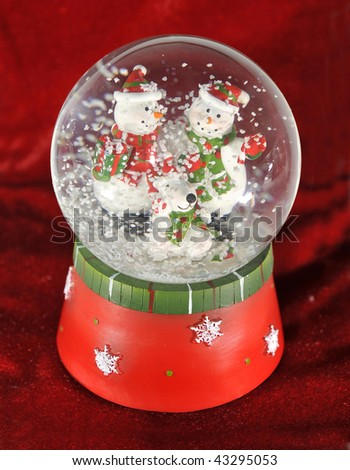 christmas themed snow globe decoration ornament with snowman and snow against crimson red velvet background. winter festive feliz navidad holiday celebration - stock photo