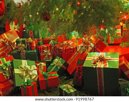 Christmas-themed wrapped gift boxes under the tree - stock photo