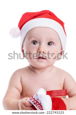 Christmas time: Baby boy isolated on white, with a red cap, holding a Christmas sock looking amazed in the distance - stock photo