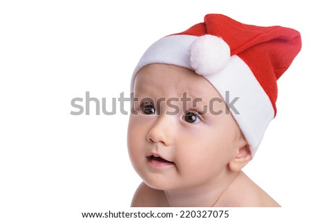 Christmas time: Baby boy isolated on white, with a red cap, looking amazed and full of expectations to the side, isolated on white - stock photo