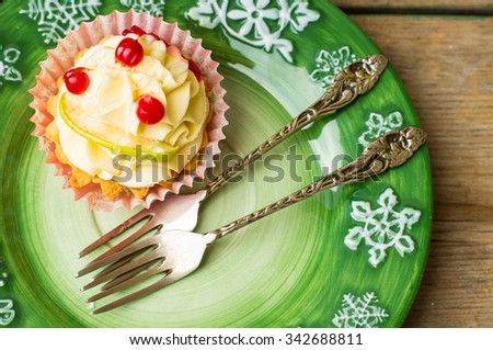 Christmas time decorations with festive decorated cupcake on the plate on rustic background - stock photo