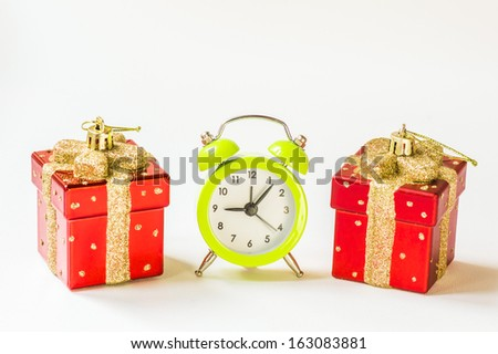 Christmas time: Green alarm clock between two present shaped Christmas decorations