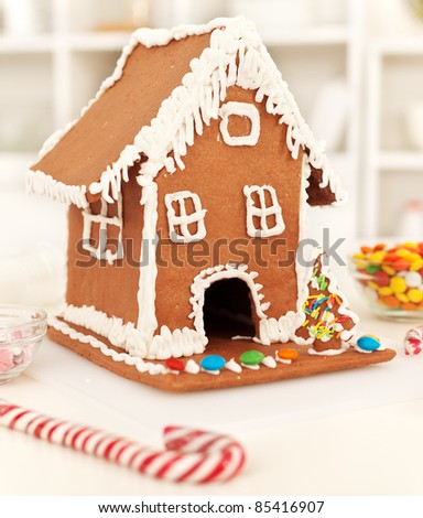 Christmas time in the kitchen with gingerbread house and candy stick - stock photo