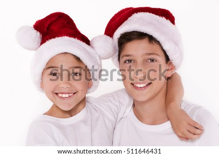 Christmas time. Two kids in Santa Claus hat smiling, looking at camera. White background. Studio shot.