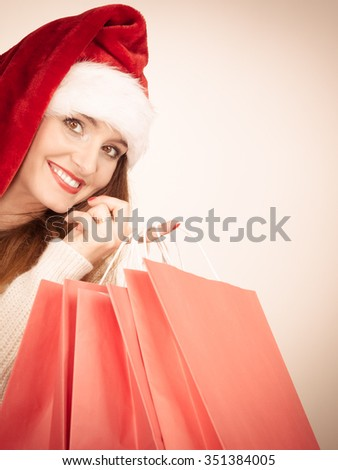 Christmas time. Young latin woman wearing santa claus hat holding red shopping bags making gifts