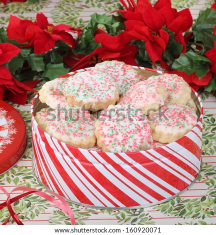 Christmas tin filled with cookies with icing and sprinkles - stock photo