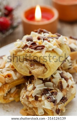 Christmas toffee buns, candles in the background - stock photo