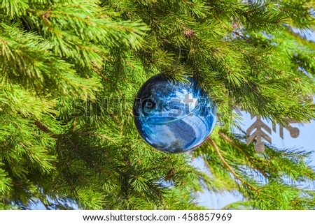 Christmas toy blue ball on the festive pine branch - stock photo