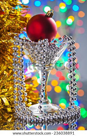 christmas toys in wineglass on mirror surface - stock photo