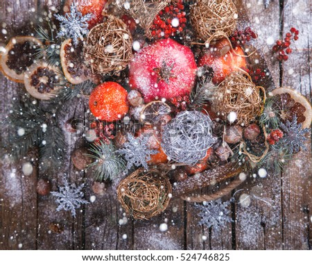 Christmas Toys,Tangerines,Nuts,Pomegranate,Cranberry,mountain Ash,Citrus,Berries in a wooden box.Festive Background.New Year Christmas card. Drawn Snowfall.selective focus.