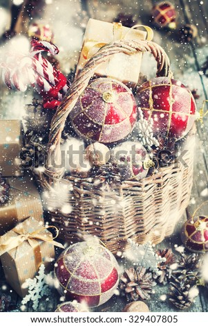 Christmas Toys with Gifts. Basket, Red balls, Pine cones, Boxes, Walnuts, Snowflakes, Sweet Candies on Wooden Table. Drawn Snowfall