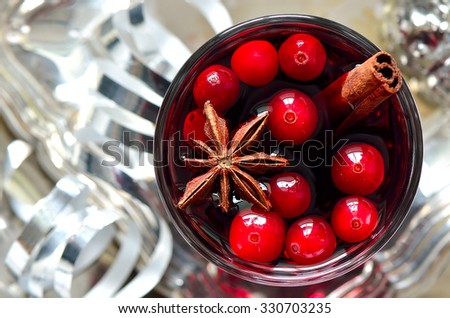 Christmas traditional warm alcohol drink or cocktail with spices and cranberries surrounded with sparkling decorations - stock photo