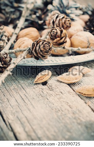 Christmas Tray with Pine cones, Walnuts, Almonds, Nuts on Wooden Background, natural holiday decoration, toned - stock photo