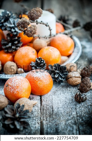 Christmas Tray with Tangerines, Pine cones, Walnuts, Almonds and Candles on Wooden Background, holiday decoration - stock photo
