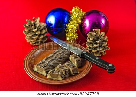 Christmas treat, chocolate covered marzipan and nougat, bar, partly cut on plate on red tablecloth. Christmas decorations on table. Selective focus on chocolate bar. - stock photo
