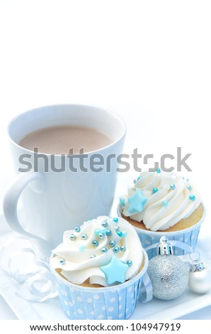Christmas treat mug of hot chocolate, frosty icy blue theme cupcake with silver xmas bauble decorations - stock photo