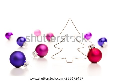 Christmas tree and baubles. Gingerbread cookie cutter and colorful christmas baubles. Shallow depth of field. - stock photo