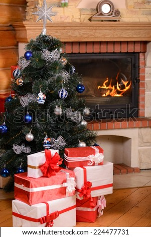 Christmas tree and boxes with gifts for family, fireplace background. - stock photo