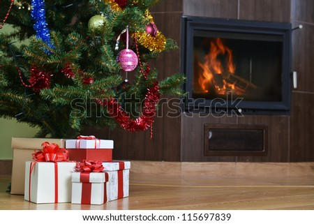 Christmas tree and christmas gift boxes in  interior with  fireplace - stock photo