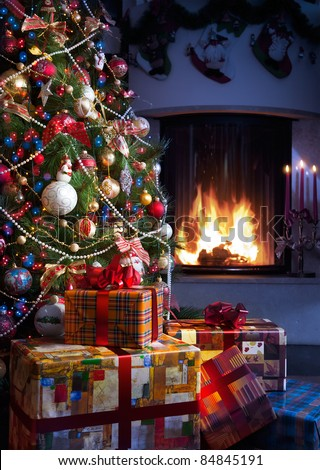 Christmas Tree and Christmas gift boxes in the interior with a fireplace - stock photo